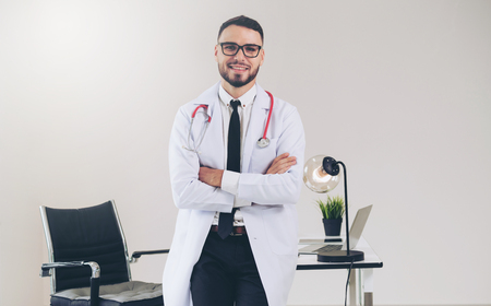 Male doctor crossed arms standing at office table in the hospital. Medical and healthcare concept.