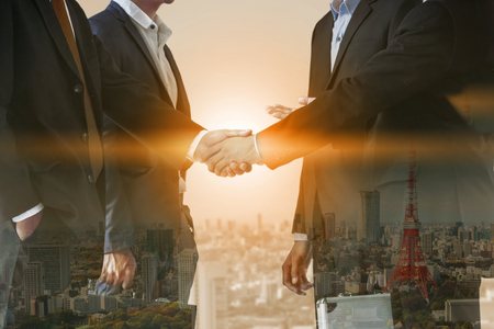 Photo pour Double exposure business people handshake agreement with cityscape in background. Business executive meeting and collaboration. - image libre de droit