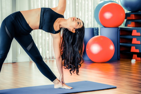Foto de Young woman practicing yoga position in an indoor gym studio. Healthy and wellness lifestyle concept. - Imagen libre de derechos