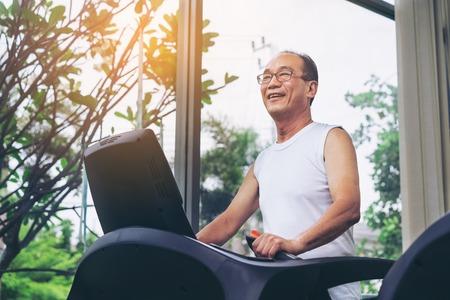 Foto de Senior man exercise on treadmill in fitness center. Mature healthy lifestyle. - Imagen libre de derechos