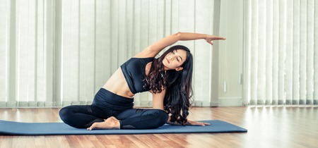 Photo pour Young woman practicing yoga position in an indoor gym studio. Healthy and wellness lifestyle concept. - image libre de droit