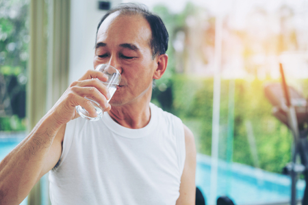 Foto de Senior man drink mineral water in gym fitness center after exercise. Elderly healthy lifestyle. - Imagen libre de derechos