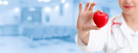 Photo pour Doctor holding a red heart at hospital office. Medical health care and doctor staff service concept. - image libre de droit