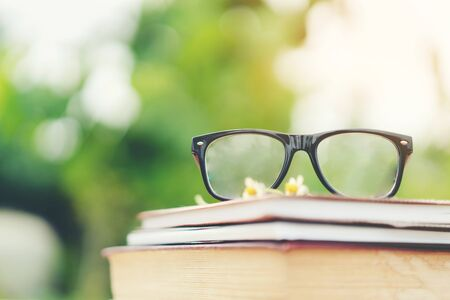 Photo pour Soft focus retro style books and eye glasses with nature background. Reading and education concept. - image libre de droit