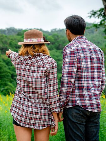Photo pour Happy couple take a romantic walk in green grass field on the hills. Travel and honeymoon concept. - image libre de droit