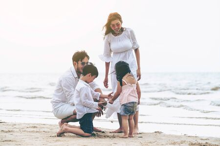Photo for Happy family of father, mother and kids goes vacation on a tropical sand beach in summer. - Royalty Free Image