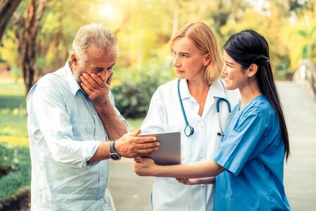 Photo for Senior man talking to doctor, nurse or caregiver in the park. Mature people healthcare and medical staff service concept. - Royalty Free Image