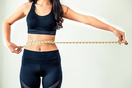Photo pour Close up shot of woman with slim body measuring her waistline and torso. Healthy nutrition and weight losing concept. - image libre de droit