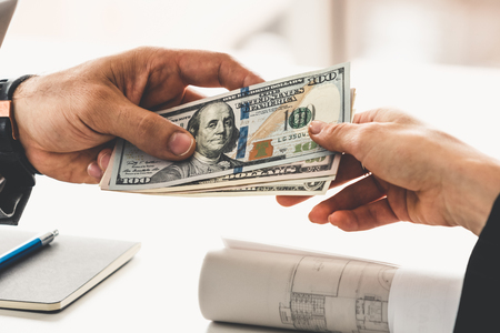 Photo pour Businessman hand sending money to another business person. Transaction, payment, salary and banking concept. - image libre de droit