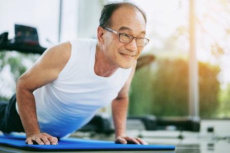 Foto de Senior man push up in fitness gym. Mature healthy lifestyle. - Imagen libre de derechos