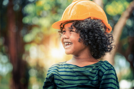 Photo pour Happy little boy engineer wearing yellow safety helmet hard hat and laughing with happiness. Education and learning concept. - image libre de droit