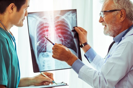 Photo pour Senior male doctor looking at x ray film of patient chest injury while working with another doctor at the hospital. Medical healthcare staff and doctor service. - image libre de droit