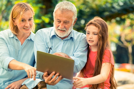 Photo pour Happy family using laptop computer together in the garden park in summer. Kid education and family activities concept. - image libre de droit