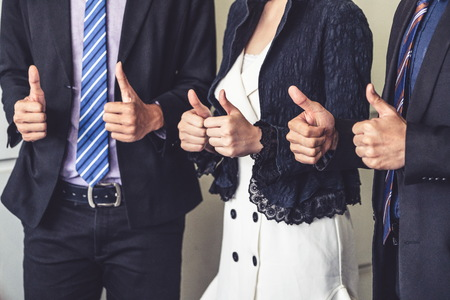 Photo pour Many happy business people make thumbs up sign join hands together with joy and success. Company employee celebrate after successful work project. Corporate partnership and achievement concept. - image libre de droit