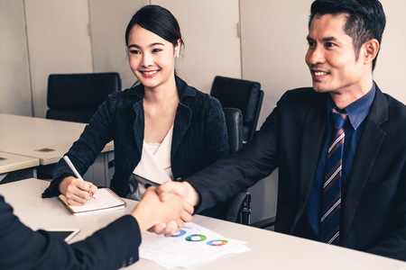 Photo for Business people agreement concept. Asian Businessman do handshake with another businessman in the office meeting room. Young Asian secretary lady sits beside him. - Royalty Free Image