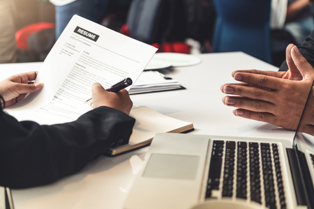 Foto de Human resources department manager reads CV resume document of an employee candidate at interview room. Job application, recruit and labor hiring concept. - Imagen libre de derechos