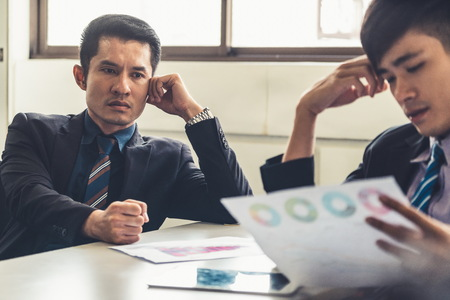 Photo pour Unhappy business manager and young businessman partner in meeting room at the office. They are under stress because of bad financial document report. Company crisis concept. - image libre de droit
