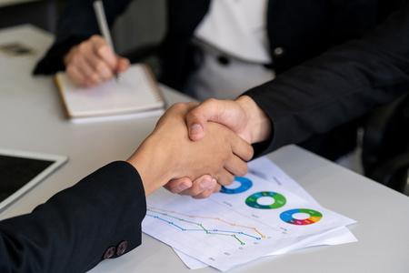 Foto de Business people agreement concept. Businessman and Asian businesswoman do handshake in the office. - Imagen libre de derechos
