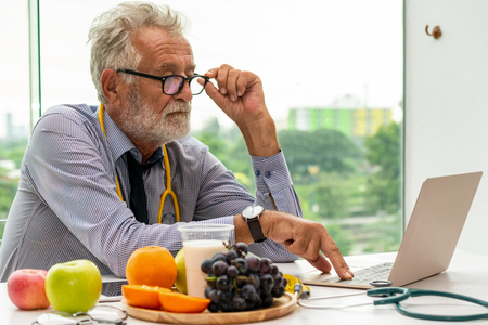 Photo pour Senior male nutritionist doctor working with laptop computer on table in the hospital office. Dieting and healthy eating concept. - image libre de droit