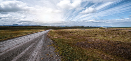 Photo pour Empty gravel dirt road through countryside landscape and grass field. Nature off road travel trip for four-wheel-drive vehicle. - image libre de droit