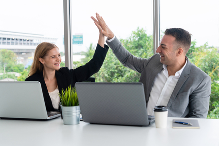 Success business partner - Businesswoman and businessman celebrating together in modern workplace office. People corporate teamwork concept.