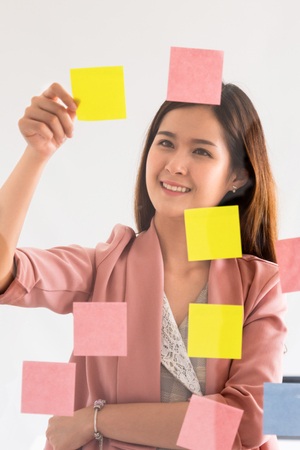 Photo pour Happy businesswoman thinking creative ideas with sticky notes on glass wall at the office. Work planning and education concept - image libre de droit