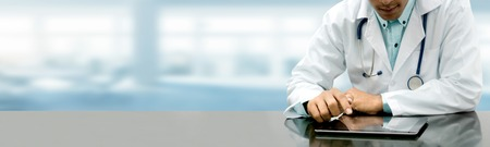 Photo pour Male doctor sitting at table with tablet computer in hospital office. Medical healthcare staff and doctor service. - image libre de droit