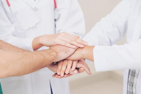 Photo pour Medical service teamwork - Doctor, surgeon and nurse join hands together. - image libre de droit