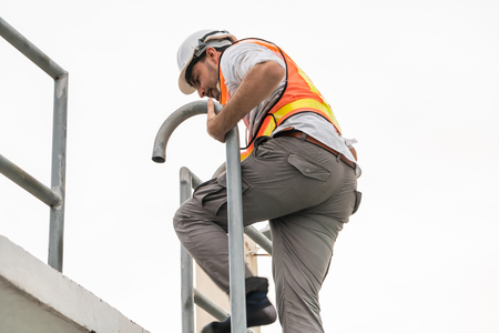 Photo pour Young man construction worker or engineer climb ladder on the building top. Engineering project concept. - image libre de droit