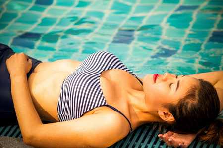 Photo pour Young relaxed woman at swimming pool in summer in luxury beach resort. Travel and lifestyle. - image libre de droit