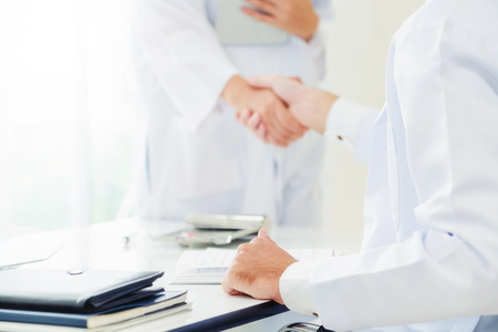 Photo pour Doctor at the hospital giving handshake to another doctor showing success and teamwork of professional healthcare staff. - image libre de droit