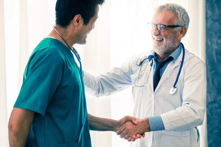 Photo pour Senior male doctor working with another doctor in hospital. Concept of medical healthcare and doctor staff education. - image libre de droit