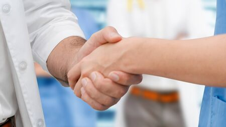 Doctor in hospital handshake with another doctor. Healthcare people teamwork and medical service concept.