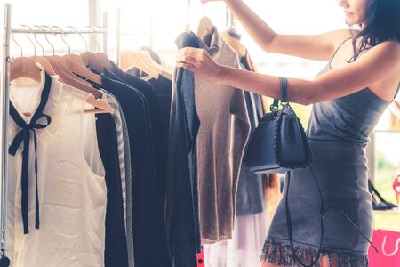 Photo pour Beautiful woman shopping for clothes at retail apparel shop in the shopping mall. Modern trade lifestyle. - image libre de droit