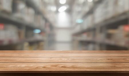 Photo pour Wood table in warehouse storage blur background with empty copy space on the table for product display mockup. Hardware goods distribution and industrial logistics concept. - image libre de droit
