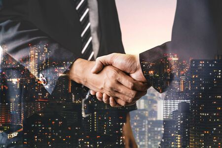 Photo pour Double exposure image of business people handshake on city office building in background showing partnership success of business deal. Concept of corporate teamwork, trust partner and work agreement. - image libre de droit