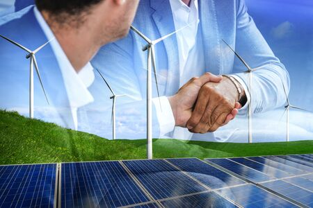 Photo pour Double exposure graphic of business people handshake over wind turbine farm and green renewable energy worker interface. Concept of sustainability development by alternative energy. - image libre de droit