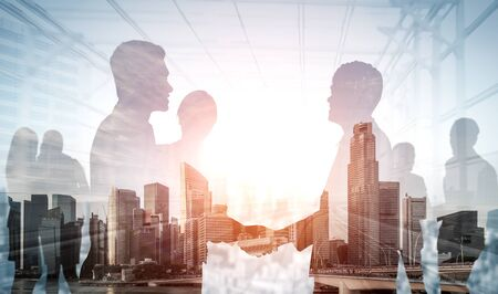 Foto de Double exposure image of many business people conference group meeting on city office building in background showing partnership success of business deal. Concept of teamwork, trust and agreement. - Imagen libre de derechos