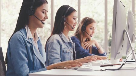 Photo for Customer support agent or call center with headset works on desktop computer while supporting the customer on phone call. Operator service business representative concept. - Royalty Free Image