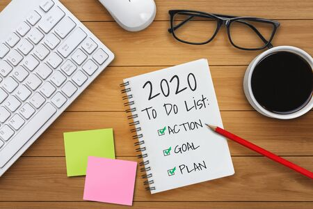Photo pour New Year Resolution Goal List 2020 - Business office desk with notebook written in handwriting about plan listing of new year goals and resolutions setting. Change and determination concept. - image libre de droit