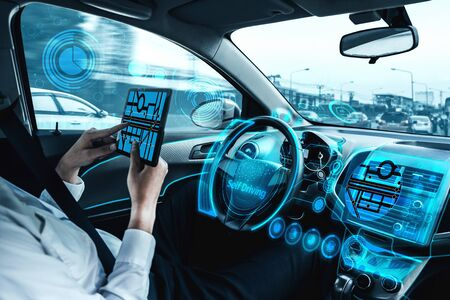 Photo pour Self-driving autonomous car with relaxed young man sitting at driver seat is driving on busy highway road in the city. Concept of machine learning, artificial intelligence and augmented reality. - image libre de droit