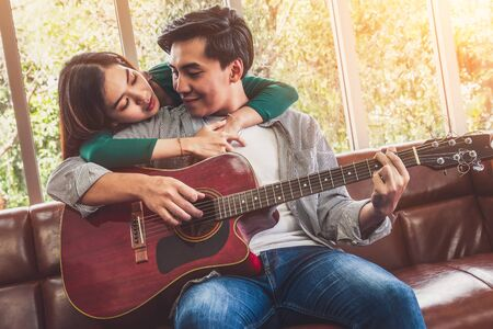 Photo pour Young Asian Couple Plays Guitar and Sing Song in Living Room at Home Together. Music and Lifestyle concept. - image libre de droit