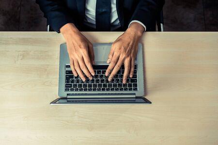 Photo pour Business person or office worker using laptop computer while sitting at desk. - image libre de droit