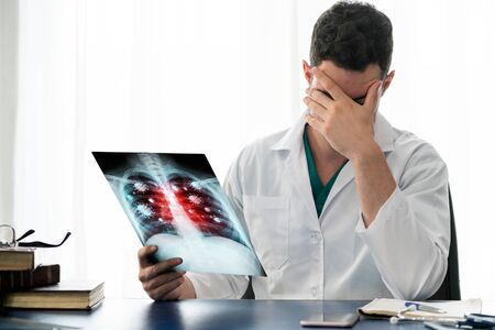 Photo pour Doctor analyze Coronavirus Disease 2019 or Covid-19 displayed on x ray film. The film shows symbol of corona virus infect patient lung and respiratory organ. Medical technology and healthcare concept. - image libre de droit