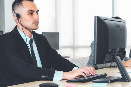 Photo pour Business people wearing headset working in office - image libre de droit