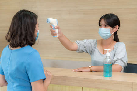Photo pour Receptionist and guest wearing face mask at front desk while having conversation in office or hospital . Covid 19 and coronavirus infection protection and protective policy concept . - image libre de droit