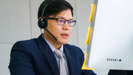 Photo for Business people wearing headset working in office to support remote customer or colleague. Call center, telemarketing, customer support agent provide service on telephone video conference call. - Royalty Free Image