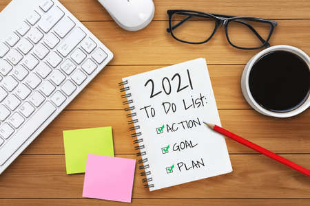 Photo for 2021 Happy New Year Resolution Goal List - Business office desk with notebook written in handwriting about plan listing of new year goals and resolutions setting. Change and determination concept. - Royalty Free Image