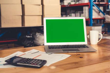 Foto de Computer with green screen display in warehouse storage room . Delivery and transportation software concept . - Imagen libre de derechos
