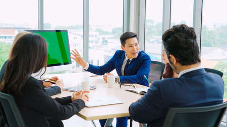 Photo pour Business people in the conference room with green screen chroma key TV or computer on the office table. Diverse group of businessman and businesswoman in meeting on video conference call . - image libre de droit